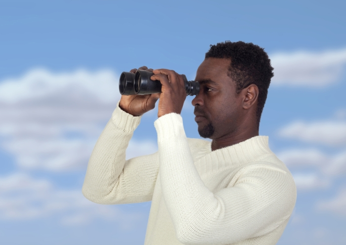 Attractive african man looking through binoculars